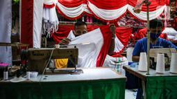 Aktivitas penjahit bendera merah putih di kiosnya, kawasan Pasar Senen, Jakarta, Rabu (5/8/2020). Menjelang peringatan HUT ke-75 Kemerdekaan RI, sejumlah pedagang mengaku penjualan pernak-pernik bendera merah putih menurun 50 persen dibanding tahun lalu akibat COVID-19. (Liputan6.com/Faizal Fanani)