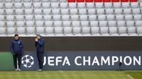 Pelatih PSG Mauricio Pochettino (kiri) dan asistennya menunggu dimulainya sesi latihan di di Munich, Jerman (6/4/2021). PSG akan bertanding melawan tuan rumah Bayern Munchen pada leg pertama babak perempat final Liga Champions di Allianz Arena. (AP Photo/Matthias Schrader)