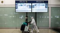 Penumpang mengenakan pakaian pelindung saat tiba di Bandara Internasional Hong Kong, Hong Kong (19/3/2020). Para penumpang di Bandara Hong Kong terpantau memakai perlindungan 'ekstra' lantaran takut tertular virus corona. (AFP/Anthony Wallace)