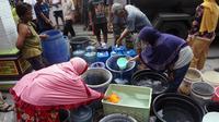 Sejumlah warga sedang menerima bantuan air bersih yang diberikan oleh Gibran Rakabuming Raka, Jumat (1/11).(Liputn6.com/Fajar Abrori)