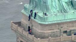 Petugas kepolisian membujuk seorang wanita yang nekat memanjat Patung Liberty di New York, Rabu (4/7). Aksi protes wanita bernama Therese Okoumou ini telah memicu ketegangan dengan para petugas berwenang selama hampir empat jam. (AFP/PIX11 News/HO)