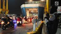 Polisi mengawasi pemudik bermotor yang masuk ke dalam kapal di Dermaga 6 Pelabuhan Merak, Banten, Kamis (22/6). Dini hari, ribuan pemudik bermotor antri menyeberang dari Pelabuhan Merak menuju Bakauheni, Lampung. (Liputan6.com/Helmi Fithriansyah)