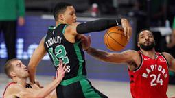 Pebasket Boston Celtics, Grant Williams, berebut bola dengan pebasket Toronto Raptors, Norman Powell, pada laga NBA di Lake Buena Vista, Senin (7/9/2020). Boston Celtics menang telak 111-89 atas Toronto Raptors. (AP/Mark J. Terrill)
