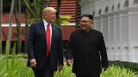 Keakraban Presiden AS Donald Trump (kiri) dengan Pemimpin Korea Utara Kim Jong-un saat berjalan di taman Hotel Capella, Pulau Sentosa, Singapura, Selasa (12/6). Trump dan Kim bertemu untuk membicarakan upaya denuklirisasi Korut. (Anthony Wallace/Pool/AFP)