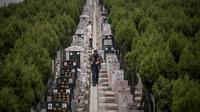 Seorang pria berjalan diantara batu nisan saat festival Qingming di sebuah pemakaman di Shanghai (6/6). Untuk orang Tionghoa, perayaan ini dilakukan untuk mengingat dan menghormati nenek moyang. (AFP/Johannes Eisele)