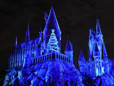 Pemandangan saat bangunan kastil Dunia Harry Potter dihiasi cahaya biru di Universal Studios Hollywood, Universal City (16/11). Proyeksi cahaya ini menjadi hiburan di Universal Studios Hollywood jelang datangnya Natal. (AFP Photo/Chris Delmas)