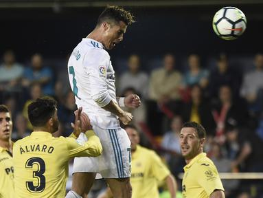 Pemain Real Madrid, Cristiano Ronaldo menyundul bola melewati adangan pemain Villarealpada laga terakhir La Liga di Ceramica stadium, Villarreal, (19/5/2018). Real Madrid bermain imbang 2-2. (AFP/Jose Jordan)