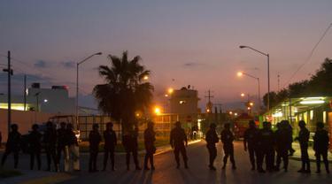 Petugas kepolisian anti huru-hara berjaga-jaga setelah terjadinya bentrokan di penjara Cadereyta di Monterrey, Meksiko, (27/3). Dikabarkan akibat kerusuhan ini setidaknya 45 orang terluka antaranya penjaga dan tahanan. (AFP Photo / Julio Cesar Aguilar)