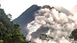 Orang-orang melihat Gunung Merapi yang memuntahkan batu dan abu di Yogyakarta (27/1/2021).  Potensi bahaya saat ini berupa guguran lava dan awan panas pada sektor selatan-barat daya meliputi sungai Boyong, Bedog, Krasak, Bebeng, dan Putih sejauh maksimal 5 kilometer.  (AFP/ Agung Supriyanto)