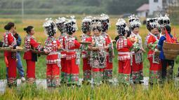 Warga yang mengenakan pakaian tradisional berkeliling untuk memperingati panen raya di Desa Dangzao, Panshi, Kota Tongren, Provinsi Guizhou, China, 20 September 2020. Berbagai aktivitas digelar di seluruh negeri untuk menyambut festival panen petani China ketiga pada 22 September. (Xinhua/Long Enze)