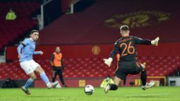 Pemain Manchester City, Phil Foden, melepaskan tendangan ke gawang Manchester United pada laga Piala Liga Inggris di Stadion Old Trafford, Rabu (6/1/2021). City menang dengan skor 2-0. (Peter Powell/Pool via AP)