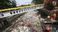 Petugas PPSU mencoba mengurai sampah yang menumpuk di Kali Cideng, Jakarta Pusat, Senin (11/9). Sempat disulap tertata rapi dan bersih, sampah plastik dan sampah rumah tangga kembali menumpuk hingga menghambat laju air. (Liputan6.com/Immanuel Antonius)