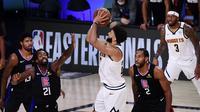 Guard Denver Nuggets Jamal Murray menembak bola di tengah kepungan pemain LA Clippers pada gim ketujuh semifinal Wilayah Barat play-off NBA di AdventHealth Arena, Selasa (15/9/2020) atau Rabu pagi WIB. (AFP/Douglas P. DeFelice)