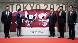 Penyelenggara berpose dengan Miraitowa dan Someity, maskot untuk Olimpiade dan Paralimpiade Tokyo 2020/2021, saat menandai 100 hari sebelum dimulainya Olimpiade di gedung Pemerintah Metropolitan Tokyo, Rabu (14/4/2021). Olimpiade Tokyo akan dibuka pada 23 Juli 2021. (AP Photo/Eugene Hoshiko, Pool)