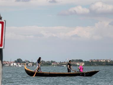 Perempuan yang tergabung dalam Row Venice menawarkan pengalaman belajar mendayung gondola di sebuah kanal di Venesia, Italia pada 16 Mei 2019. Row Venice merupakan organisasi nonprofit bentukan sekelompok perempuan yang berfokus pada pelestarian seni mendayung perahu. (MARCO BERTORELLO/AFP)