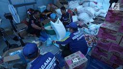 Relawan Tagana memasukan beras dan mie instan untuk Warga korban gempa dan tsunami Palu di kantor Dinas Sosial, Palu, Sulawesi Tengah, Minggu (7/10). Warga antre sejak pagi untuk mendapatkan bantuan yang disalurkan dari Dinsos. (Liputan6.com/Fery Pradolo)
