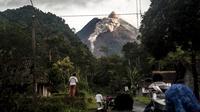 Orang-orang melihat Gunung Merapi yang memuntahkan batu dan abu di Yogyakarta (27/1/2021). BPPTKG menyatakan pada tanggal 27 Januari 2021 telah terjadi awan panas guguran di Gunung Merapi dengan jarak luncur maksimal 1200 meter ke arah hulu Sungai Krasak. (AFP/ Agung Supriyanto)