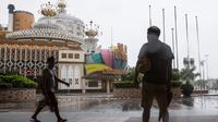 Pejalan kaki melintas dekat Kasino Lisboa yang telah ditutup menyusul ancaman Topan Mangkhut di Makau, Minggu (16/9). Pihak berwenang Makau memutuskan menutup 42 kasino yang telah disetujui pemerintah kota dan para pemilik tempat judi (AFP/ISAAC LAWRENCE)
