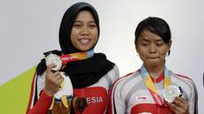 Pebalap sepeda Indonesia, Sri Sugiyanti dan Ni'mal Maghfiroh, saat pembagian medali pada Asian Para Games di Velodrome, Jakarta, Kamis (11/10/2018). Pasangan ini meraih medali perak di nomor trek Individual Pursuit B putri. (Bola.com/M Iqbal Ichsan)