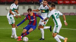 Striker Barcelona, Francisco Trincao (tengah) menguasai bola dikepung tiga pemain Elche dalam laga lanjutan Liga Spanyol 2020/21 pekan ke-24 di Camp Nou Stadium, Barcelona, Rabu (24/2/2021). Barcelona menang 3-0 atas Elche. (AP/Joan Monfort)