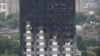 Kerusakan bangunan apartemen Grenfell Tower di London terlihat dari utara Kensington, Minggu (18/6). Gedung apartemen Grenfell Tower yang terbakar pada lepas tengah malam Rabu 14 Juni 2017 lalu dikhawatirkan roboh usai habis dilahap api. (TOLGA AKMEN/AFP)