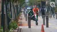 Seorang pria mengendarai skuter listrik di trotoar Jakarta, Jumat (22/11/2019). Tidak ada sanksi dari Pemprov DKI Jakarta terhadap pengguna skuter listrik selama regulasi yang mengatur masih dalam pembahasan. (merdeka.com/Imam Buhori)