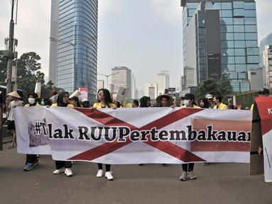 Mahasiswa Universitas Indonesia (UI) membawa spanduk saat menggelar kampanye Bahaya Merokok di car free day (CFD), Jakarta, Minggu (6/5). Dalam aksinya, mahasiswa menolak RUU Pertembakauan. (Merdeka.com/Iqbal Nugroho)