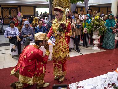 Pasangan pengantin saat mengikuti nikah massal di Surabaya, Jawa Timur, Rabu (18/12/2019). Sebanyak 60 pasangan pengantin mengikuti nikah massal yang digelar Dinas Sosial Kota Surabaya. (JUNI KRISWANTO/AFP)