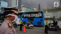 Petugas polisi mengimbau pengguna kendaraan saat melakukan Pengawasan Pelaksanaan PSBB di kawasan Bundaran HI, Jakarta, Senin (13/4/2020). Petugas juga mengimbau mengatur posisi duduk dan pembatasan penumpang untuk kendaraan bermobil baik pribadi maupun angkutan umum. (Liputan6.com/Faizal Fanani)