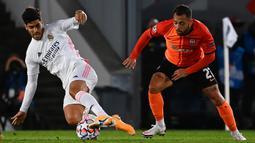 Penyerang Real Madrid, Marco Asensio, berebut bola dengan gelandang Shaktar Donetsk, Maycon, pada laga Liga Champions 2020/2021 di Estadio Alfredo Di Stefano, Rabu (21/10/2020) malam WIB. Real Madrid kalah 2-3 oleh Shaktar Donetsk. (AFP/Gabriel Bouys)