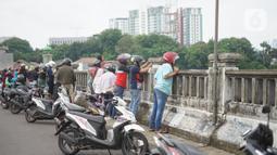Pengendara sepeda motor mengamati banjir yang menggenangi kawasan Rawajati dari atas flyover di Jakarta Timur, Rabu (1/1/2020). Banjir yang berasal dari luapan Sungai Ciliwung itu menjadi daya tarik tersendiri bagi sebagian pemotor yang melintasi di flyover tersebut. (Liputan6.com/Immanuel Antonius)