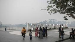 Warga beraktivitas saat asap kebakaran lahan gambut menyelimuti alun-alun Kabupaten Siak, Riau, Kamis (12/9/2019). Asap pekat kebakaran lahan gambut tersebut selain mengganggu kesehatan serta mencemari udara sehingga kualitasnya turun ke status tidak sehat. (Liputan6.com/Faizal Fanani)