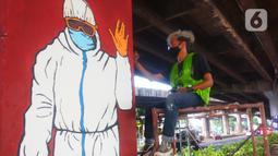 Mahasiswa melukis mural bertemakan sosialisasi pencegahan Covid-19 di kolong jalan tol dalam kota, Kebun Nanas, Jakarta, Jumat (4/12/2020). Kegiatan membuat mural ini dalam rangka mengkampanyekan pola hidup sehat 3m. (merdeka.com/Arie Basuki)