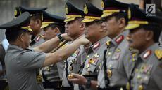 Kapolri Jenderal Tito Karnavian menyematkan tanda pangkat kepada Brigjen Pol Teddy Minahasa pada pelantikan Kadiv Propam Polri dan enam kapolda di Rupatama Mabes Polri, Senin (20/8). Teddy dilantik menjadi Kapolda Banten. (Merdeka.com/Iqbal S. Nugroho)