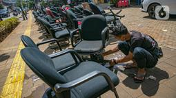 Karyawan membersihkan peralatan kantor pascabanjir di salah satu bank swasta di Kemang, Jakarta, Selasa (23/2/2021). Karyawan pertokoan, perkantoran, hingga perbankan mulai membersihkan sisa lumpur dari banjir yang melanda kawasan tersebut pada 20 Februari 2021 lalu. (Liputan6.com/Faizal Fanani)