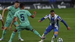 Pemain Espanyol Raul de Tomas (kanan) menggiring bola melewati pemain Real Madrid Raphael Varane pada pertandingan La Liga Spanyol di Stadion Cornella-El Prat, Barcelona, Spanyol, Minggu (28/6/2020). Real Madrid menang 1-0 dan menggeser Barcelona dari puncak klasemen. (AP Photo/Joan Monfort)