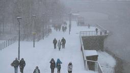 Pejalan kaki berjalan di tepi sungai Thames saat hujan salju melanda London (27/2). Cuaca ekstrem yang melanda sebagian wilayah Eropa menyebabkan warga dan wisatawan mengalami sakit dan beberapa meninggal akibat kedinginan. (AFP Photo/Daniel Leal-Olivas)