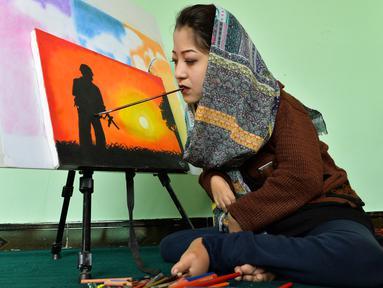 Foto yang diambil pada 5 Desember 2019 menunjukkan seniman Robaba Mohammadi melukis menggunakan mulut di studionya di Kabul. Gadis 19 tahun itu dilahirkan  dengan kelumpuhan parsial anggota tubuhnya sehingga tidak mampu mengendalikan tangan dan kakinya. (NOORULLAH SHIRZADA/AFP)