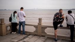 Orang-orang berdiri di pinggir pantai menghadap Jembatan Hong Kong-Zhuhai-Makau (HKZM) di Zhuhai (22/10). Jembatan laut terpanjang di dunia yang menghubungkan Hong Kong, Makau, dan daratan Cina ini akan dibuka 24 Oktober 2018. (AFP Photo/Fred Dufour)