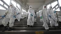 Pekerja memakai alat pelindung semprotan disinfektan untuk membantu mencegah penyebaran Virus Corona COVID-19, di stasiun kereta bawah tanah di Seoul pada 12 Maret 2020. (YONHAP / AFP)