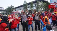 Para polisi menari menemani para demonstran saat peringatan Hari Buruh Sedunia di depan Gedung Sate Bandung.