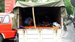 Sejumlah warga korban banjir di Grogol menjadikan truk sebagai tempat penampungan sementara, Rabu (11/2/2015).(Liputan6.com/Faisal R Syam)