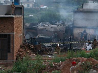Pejabat militer Pakistan memeriksa lokasi kecelakaan pesawat di Rawalpindi, Pakistan, Selasa (30/7/2019). Sebuah pesawat militer Angkatan Darat Pakistan jatuh di Rabi Center di Rawalpindi. (AP Photo/Anjum Naveed)