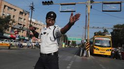 Polisi lalu lintas India, Ranjeet Singh arus kendaraan bermotor di persimpangan yang sibuk di Indore pada 18 November 2019. Singh yang memiliki kumis ala Freddie Mercury ini mengatur lalu lintas sambil menari juga bergerak menghindari bajaj dan truk yang melintas. (AP/Aijaz Rahi)
