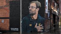 Mural pelatih klub Liverpool, Jurgen Klopp di Jamaica Street, pusat kota Baltic Triangle di Liverpool, Senin (10/12). Banyak yang menyambut baik pembuatan mural itu namun tidak sedikit pula yang mencibir, termasuk suporter klub Everton. (Paul ELLIS / AFP)