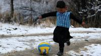 Seorang anak laki-laki Afghanistan, Murtaza Ahmadi berkaos kantong kresek timnas Argentina milik Lionel Messi terlihat bermain bola di  kabupaten Jaghori, provinsi Ghazni, 29 Januari 2016. Sebelumnya, foto Murtaza itu menyebar luas di dunia maya (STR/AFP)