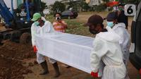 Petugas mengangkat peti jenazah Covid-19 untuk dimakamkan dengan prosedur covid 19 di TPU Tegal Alur, Jakarta, Minggu (3/12/2021). Sebanyak 625.518 kasus dinyatakan sembuh dan 22.555 orang meninggal dunia. (Liputan6.com/Angga Yuniar)