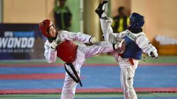 Dua peserta perempuan saat bertarung dalam Kejuaraan Terbuka Taekwondo di Banda Aceh (17/7/2019). Ratusan peserta mengikuti turnamen yang memperebutkan Piala Pemerintah Aceh. (AFP Photo/Chaideer Mahyuddin)