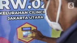 Warga menempelkan kartu pada mesin ATM saat mengambil bantuan beras di Kantor RW 02, Kelurahan Cilincing, Jakarta Utara, Rabu (17/3/2021).  Program ini dibagikan secara berkala selama 2 kali dalam sebulan dengan jatah masing-masing 3 kilogram beras per orang. (merdeka.com/Iqbal S. Nugroho)