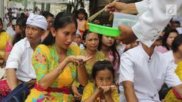 Pemuka agama Hindu memberikan air suci saat upacara Tawur Kesanga di Pura Aditya Jaya, Rawamangun, Jakarta, Jumat (16/3). (Liputan6.com/Arya Manggala)